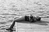 Man resting on a dock by a lake
