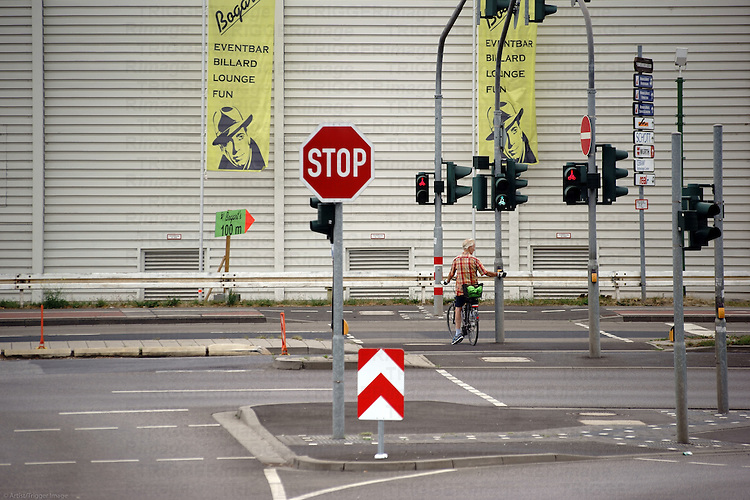 A bicycle rider stands at a red light intersection on a street with many traffic signs.
