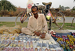 A man sells shoes along a street in Lahore, Pakistan....