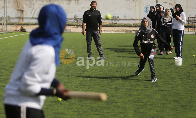 """Palestinian girls take part in Baseball training, in Gaza city, on February 20, 2017. Baseball is a bat-and-ball game played between two teams of nine players each, who take turns batting and fielding. Baseball is thought to have originated as a game called """"rounders"""" in England and gained popularity in the United States in the early 1900s. It has gone by many names in the past, including """"town ball,"""" """"goal ball,"""" round ball,"""" and simply """"base,"""" just to name a few. Photo by Ashraf Amra"""