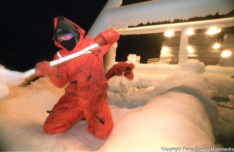 """Fighting 50 knot winds and freezing conditions, skipper of the fishing vessel """"Kiska Sea"""", Mike Wilson, uses a shovel to break ice and rid the boat of over two feet of ice which formed as a result of freezing spray coming over the sides while fishing for opilio crab in the  Bering Sea in January and February of 1995.  Realizing the danger, Wilson took the boat up to the ice pack where it sat while he and the crew beat ice for 24 hours. Boats which form too much ice risk becoming too top heavy and capsizing.  Freezing spray is caused when wind blows sea spray onto the boat and it freezes on inpact to anything it touches. The Bering Sea is known for having the worst storms in the world.  Nights are long and cold in the arctic in the winter.  Crab fishing in the Bering Sea is considered to be one of the most dangerous jobs in the world.  This fishery is managed by the Alaska Department of Fish and Game and is a sustainable fishery.  The Discovery Channel produced a TV series called """"The Deadliest Catch"""" which popularized this fishery."""