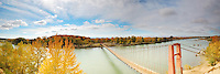Panorama landscape fine art photography of Xinjiang autumn scenery surrounded by gorgeous colorful trees. A red hanging bridge can be seen connecting both riverside over the cold water river. China outdoor landscape photography by Paul Chong.