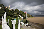 "Portmeirion, in North Wales, is a resort, where no one has ever lived. A self-taught Welsh architect named Sir Clough Williams-Ellis built it out of architectural salvage between the 1920s and 1970s, loosely based on his memories of trips to Portofino. Including a pagoda-shaped Chinoiserie gazebo, some Gothic obelisks, eucalyptus groves, a crenellated castle, a Mediterranean bell tower, a Jacobean town hall, and an Art Deco cylindrical watchtower. He kept improving Portmeirion until his death in 1978, age 94. It faces an estuary where at low tide one can walk across the sands and look out to sea. At high tide, the sea is lapping onto the shores. Every building in the village is either a shop, restaurant, hotel or self-catering accomodation. The village is booked out at high season, with numerous wedding receptions at the weekends. Very popular amongst the English and Welsh holidaymakers. Many who return to the same abode season after season. Hundreds of tourists visit every day, walking around the ornamental gardens, cobblestone paths, and shopping, eating ice-creams, or walking along the woodland and coastal paths, amongst a colourful assortment of hydrangea, rhododendrons, tree ferns and redwoods. The resort boasts two high class hotels, a la carte menus, a swimming pool, a lifesize concrete boat, topiary, pools and wishing wells. The creator describes the resort as ""a home for fallen buildings,"" and its ragged skyline and playful narrow passageways which were meant to provide ""more fun for more people."" It does just that.///Promenade, at Hotel Portmeirion,  with statues overlooking the estuary, the swimming pool and the village behind on the hill"
