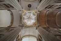 Looking up at the lantern tower, built at the junction of the barrel-vaulted ceilings of the nave and transept, after the collapse of the original cupola in the 15th century, in the Abbatiale Sainte-Foy de Conques or Abbey-church of Saint-Foy, Conques, Aveyron, Midi-Pyrenees, France, a Romanesque abbey church begun 1050 under abbot Odolric to house the remains of St Foy, a 4th century female martyr. On the keystone is the coat of arms of Louis de Crevant, abbot of Conques 1482-96. The church is on the pilgrimage route to Santiago da Compostela, and is listed as a historic monument and a UNESCO World Heritage Site. Picture by Manuel Cohen