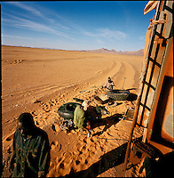 Sahara desert, Libya-Chad, November/December 2004..Every week, a convoy of 40 privately owned Libyan trucks loaded by the WFP with about 1000 metric tons of western food aid cross 2500 km of deep desert across Libya and Chad to reach more than 200 000 refugees from Darfur in camps near the Sudanese border. Fixing a tire puncture, one of many...