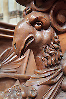 Carved wooden choir stall with a goat's head under the armrest, in Saint Volusian Abbey, or the Abbatiale Saint-Volusien, in Foix, Ariege, Midi-Pyrenees, France. The 26 choir stalls were acquired in 1804 from Saint-Sernin church, and were built in 1670 for the chapter of Toulouse. The original abbey church was built in the 12th century, but was later destroyed and rebuilt in the 17th century. The abbey houses the relics of St Volusian, 7th bishop of Tours, who died c. 495 AD, and its buildings now house the Prefecture of the Ariege. Picture by Manuel Cohen