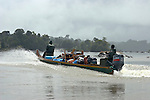 The Marowijne River, Suriname.  A boat laden with furniture heads upriver through the rapids.