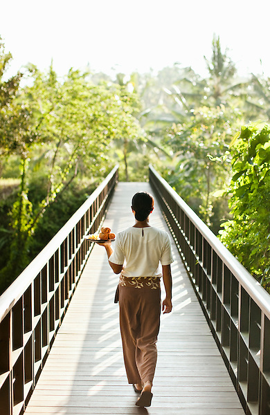 A woman carries a tray of cold towels across the bridge that connects the resort to Kayumanis Spa, Kayumanis Ubud, Bali, Indonesia.