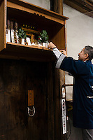 """Tokubee Masuda, CEO of the Tsukinokatsura sake brewery attending to the brewery's shinto shrine. Fushimi, Kyoto, Japan, October 10, 2015. Tsukinokatsura Sake Brewery was founded in 1675 and has been run by 14 generations of the Masuda family. Based in the famous sake brewing region of Fushimi, Kyoto, it has a claim to be the first sake brewery ever to produce """"nigori"""" cloudy sake. It also brews and sells the oldest """"koshu"""" matured sake in Japan."""