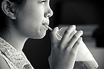 A young asian woman sipping on iced coffee through a straw in summer