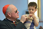 Cardinal Timothy Dolan, the archbishop of New York, compares crosses with 4-year old Yusef Wesam inside the Chaldean Catholic Cathedral of St. Joseph in Ankawa, near Erbil, Iraq, on April 9, 2016. The boy was displaced by ISIS in 2014.<br /> <br /> Dolan, a board member of the Catholic Near East Welfare Association, is in Iraqi Kurdistan with other church leaders to visit with Christians and others displaced by ISIS.<br /> <br /> CNEWA is a papal agency providing humanitarian and pastoral support to the church and people in the region.
