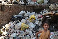 2011 Mokattam Garbage City (alla periferia del Cairo) il quartiere copto dove si vive in mezzo alla spazzatura raccolta: mezzo busto di una bambina sorridente. Dietro di lei montagne di rifiuti.