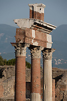 Colonnade around the Forum, Pompeii, 2nd century BC and surrounded by colonnades. Lit by the strong afternoon sun a group of Corinthian columns stands against the misty mountainous background