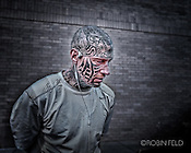 photo of man with tatoos on head and face