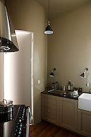 In the kitchen the cupboards have been designed in a Shaker style and painted a subtle grey-green