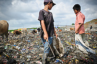 Taupik, 14, talking with a friend on the active section of the 'Trash mountain', Makassar, Sulawesi, Indonesia.