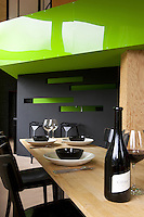 The pine table in the dining area is set at an angle beneath the lime green lacquered panelling of the mezzanine