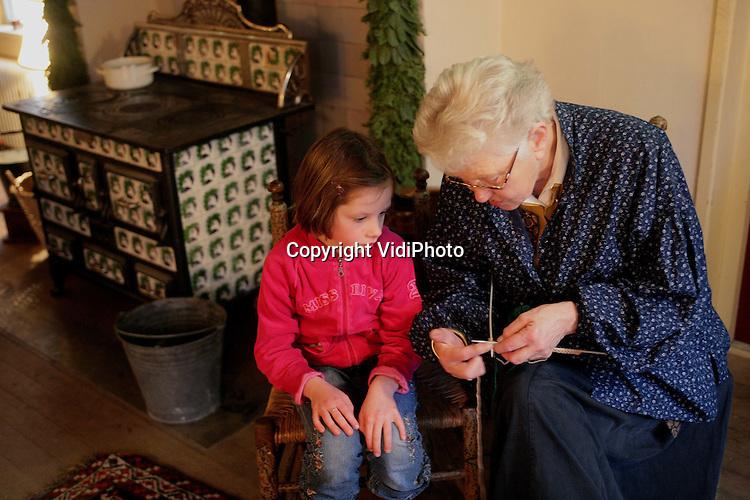 """Foto: VidiPhoto..ARNHEM - Breien is weer in. Dat constateert het Nederlands Openluchtmuseum, waar zes dames op dit moment tijdens de winteropenstelling in twee ploegen .dagelijks breiles geven aan kinderen. Jarenlang was breien """"not done"""", maar nu is het volgens de 'oma's'weer ongekend populair. Opvallend is dat jongens de techniek zelfs sneller onder de knie hebben dan meisjes."""