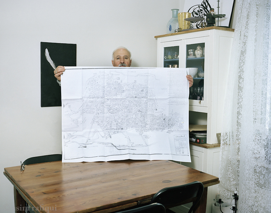 Amil Sarsour, from Safad, Palestine, whose family left their home city of Safad in 1948. Amil was born in the camps in a refugee camp in Syria in 1956. Amil holds up an artists drawing of the town of Safad as it looked in the 1940s. Amil used this map when he last visited Safad now in Israel, and also offered the Azaan, the Muslim call to prayer, outside his father's home. He tells of being surrounded by a hostile crowd which was only held back by an elderly Jewish man who happened to have rememnered Amil's grandfather and warned the people to not stop Amil. 'This is his family's house. He is not come to take it from you', the old man shourted at the crownd.' Let him say his prayers. We stole this from them. Now he just wants to pay his respects'.
