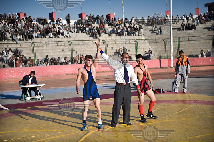 The referee declares the winner at the Olympic Stadium in Kabul, where the national wrestling championship is taking place. Young men from across the provinces have come to Kabul to participate.