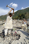 Following an October 8, 2005, earthquake, men in Balakot dig into the rubble of their house, which collapsed in the disaster.