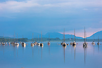 Yachts moored on Loch Creran, making reflections on the sea loch at sunset on west coast of Scotland, near Creagan in the Argyll and Bute region