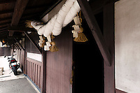 """Shinto paper and straw ropes at the entrance to the Tsukinokatsura sake brewery, Fushimi, Kyoto, Japan, October 10, 2015. Tsukinokatsura Sake Brewery was founded in 1675 and has been run by 14 generations of the Masuda family. Based in the famous sake brewing region of Fushimi, Kyoto, it has a claim to be the first sake brewery ever to produce """"nigori"""" cloudy sake. It also brews and sells the oldest """"koshu"""" matured sake in Japan."""