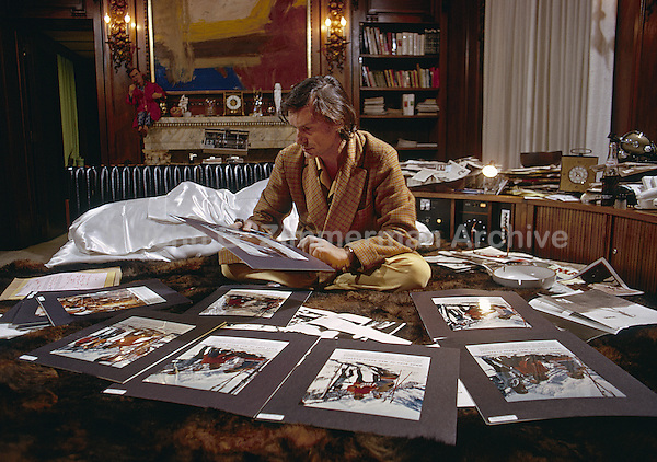 Hugh Hefner in bed reviewing Playboy magazine layouts. Chicago, 1973. Color Photo by John G. Zimmerman
