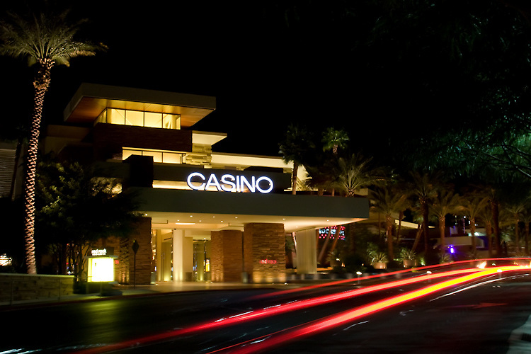 A car passes by the entrance to a casino late at night.