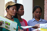Women in the village of A Luoi, Vietnam read brochures at the local People's Committee headquarters about programs to assist farmers who are victims of Agent Orange and bombs and land mines left over from the Vietnam War. April 25, 2013.