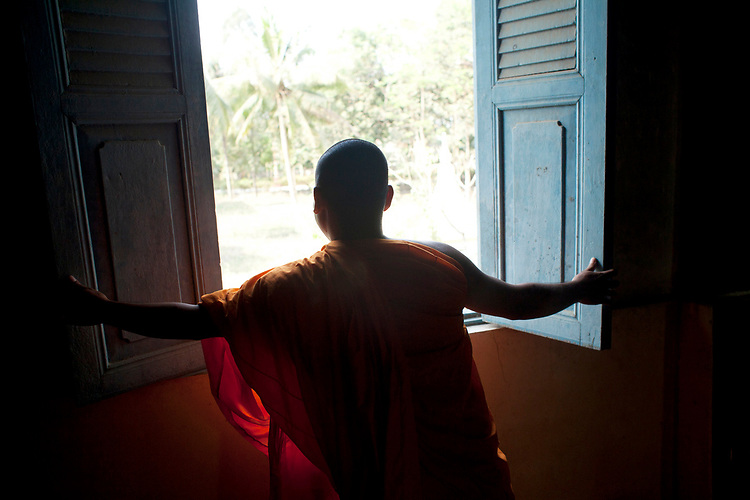 A monk opens a window in a small village temple outside of Phnom Penh, Cambodia. <br /> <br /> Photos &copy; Dennis Drenner 2013.