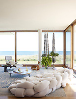 All of the rooms in the house have been placed to maximise the coastal views across the grassy dunes and out to sea. In this living room, woven plant holders have been hung in the window, echoing the foliage outside