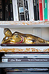 A reclining Buddha figure rests on the bookcase at the home of Francoise Morechand  in Tokyo, Japan on Dec. 8 2010.