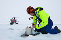 Scientist installing a portable seismometer on an ice floe to record seismic waves that travel up through the ocean from the seafloor to the ice floe, Arctic Ocean.