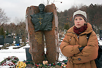 Moscow, Russia, 27/11/2005..Moskovskii Komsomolyets journalist Katya Deyeva by the grave of Dimitri Kholodkov, a  MK war correspondent killed in a 1994 explosion in the MK newsroom when he opened a booby-trapped briefcase which he believed contained evidence of corruption in the Russian Army. Katya was standing beside him but escaped with minor injuries because she was shielded from the blast by Kholodkov's body.
