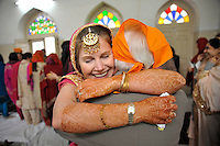 After the wedding ceremony of British/Punjabi couple Lindsay and Navneet Singh, the bride hugs her father with henna patterns on her arm at the reception at Grewal Farms in Amritsar.