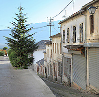 Street off the Qafe or Neck of the Bazaar, a busy intersection of 5 streets that forms the heart of the old town of Gjirokastra, Southern Albania. Most of the Ottoman houses date from the 17th and 18th centuries. Gjirokastra was settled by the Greek Chaonians, the Romans and Byzantines before becoming an Ottoman city in 1417. Its old town was listed as a UNESCO World Heritage Site in 2005. Picture by Manuel Cohen