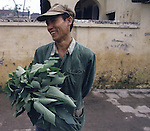 A farmer poses with an armload of vegetables in Hanoi, North Vietnam.  (Jim Bryant Photo).....