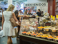 Customers choose spices in a kiosk in the former Nabisco bakery in New York, now the trendy Chelsea Market, on Friday, July 17, 2015. The owners of the building, Jamestown Properties converted the building into a food arcade and office building in the 1990's t. (© Richard  B. Levine)