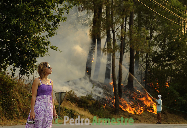 A woman is seen around the area where a fire burns, in Salvador nord of Portugal, on august 09, 2010. (c) Pedro ARMESTRE