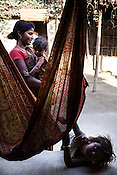 21 year old Asha Devi holds her 11 month daughter, Sita Mandal while her 3 year old son, Gaurav Mandal plays in her house in Bhardaha in Saptari, Nepal.