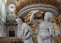 Statues representing Faith, Hope and Charity supporting the pulpit, carved in wood then painted and gilded in 1773, designed by Pierre-Joseph Christophle, 1715-1782, on the north side of the nave in the Basilique Cathedrale Notre-Dame d'Amiens or Cathedral Basilica of Our Lady of Amiens, built 1220-70 in Gothic style, Amiens, Picardy, France. Behind is the main Western facade with its Grand Organ, installed 1549, and rose window. Amiens Cathedral was listed as a UNESCO World Heritage Site in 1981. Picture by Manuel Cohen