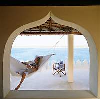 A girl relaxing in a hammock hanging from the makuti roof of the terrace with a view over the sea