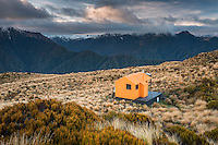 Sunrise over mountains and Mt. Brown Hut, West Coast, South Westland, New Zealand