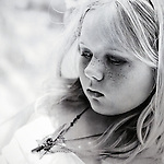 Closeup black and white portrait of a young girl with freckles looking sad