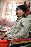 Li Yan sits in her wheel-chair in her home in Yinchuan, Ningxia Province, China, on May 7, 2007. 28-year-old Li Yan suffers from motor neuron disease also known as amyotrophic lateral sclerosis (or ALS), the same illness that has thereotical physicist Stephen Hawking. Li Yan asked China's National People's Congress (NPC) to consider a draft on euthanasia. Photo by Lucas Schifres/Pictobank