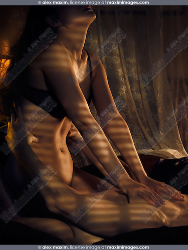 Man and a woman making love in bed lit by dim light coming through window blinds