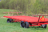 Red metal hay wagon in field