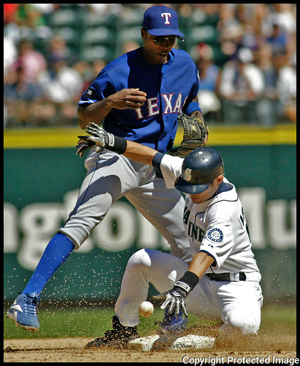 Seattle Mariners Ichiro Suzuki breaks up a double play b y forcing Texas Rangers second baseman Alfonso Soriano to drop the ball in the eight inning of their major league game at Safeco Field Sunday, July 3, 2005 in Seattle. Mariners Willie Bloomquist scored on the play as the Mariners beat the Rangers 2-1. ( AP PHOTO/Jim Bryant)