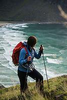Female hiker hiking up trail with Kvalvika beach in background, Moskenesoy, Lofoten Islands, Norway